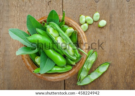 Bowl of fresh podded broad beans on a wooden table. Healthy organic food. Top view.