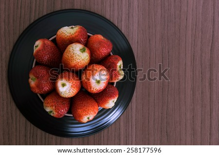 Bowl of fresh succulent strawberries over wood - stock photo