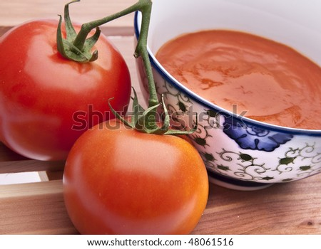Bowl of fresh tomato soup with tomatoes on a cedar plank background.