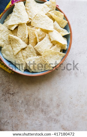 Bowl of fresh tortilla chips on stone surface with copy space.  View from above - stock photo