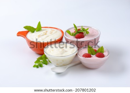 bowl of fresh yogurt with pieces of tropical fruits on white background