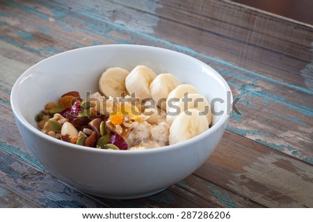 Bowl of freshly prepared home made porridge oatmeal topped with sliced banana and dried fruit, nuts and seeds. A healthy breakfast served on a rustic wooden tray.  - stock photo