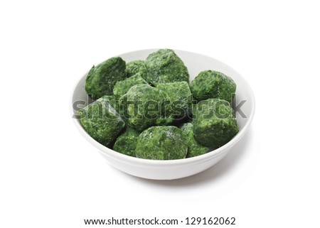 Bowl of frozen spinach isolated on white - stock photo