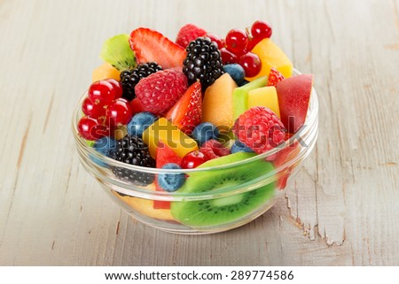bowl of fruit salad isolated on wood table - stock photo