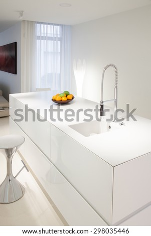 Bowl of fruits on white worktop in modern kitchen - stock photo