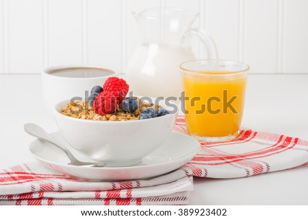 Bowl of granola and berries with coffee and orange juice. - stock photo