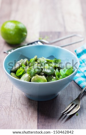 Bowl of green boiled broad beans, salad with broad beans, garlic and lime - stock photo