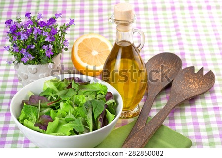 bowl of green salad and seasoning on checkered tablecloth - stock photo