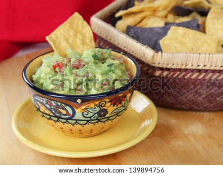 Bowl of guacamole dip with basket of tortilla chips. - stock photo