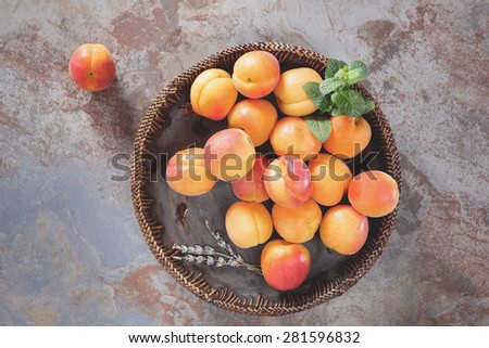 Bowl of harvested apricots.  Fresh apricots in wooden bowl on old rustic background decorated with mint and lavender flower. Top view, rustic style. Natural light - stock photo