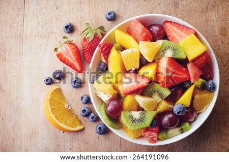 Bowl of healthy fresh fruit salad on wooden background. Top view. - stock photo