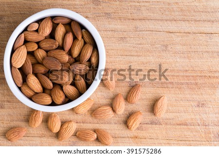 Bowl of healthy fresh raw shelled almonds with some spilling out on an old wooden board with copy space viewed from above - stock photo