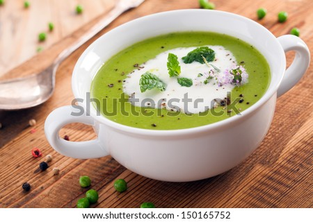 Bowl of healthy green pea soup topped with cream and fresh herbs served as a starter - stock photo