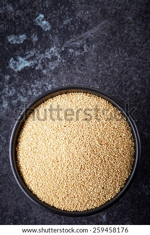 bowl of healthy white amaranth seeds on dark background, top view - stock photo