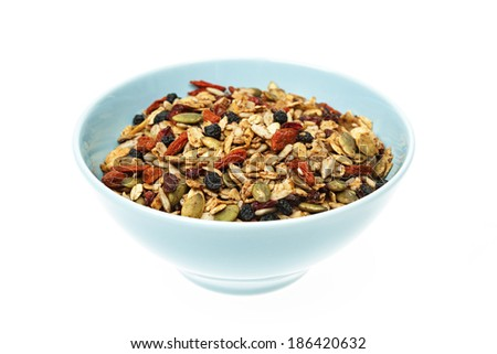 Bowl of homemade granola with various seeds and berries isolated on white background - stock photo