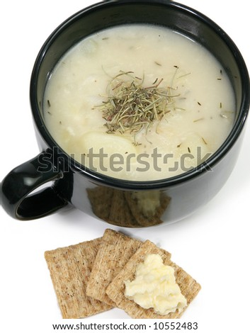 Bowl of homemade herb potato soup and wheat crackers with butter.