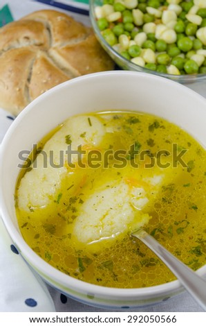 Bowl of homemade soup with noodles and plate of vegetables served with homemade bread