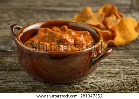 Bowl of homemade steak chili on a rustic background. - stock photo