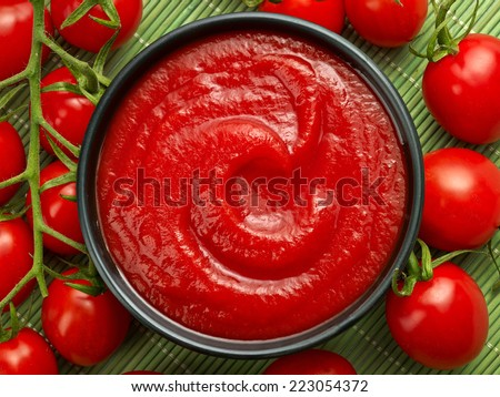 bowl of ketchup or tomato sauce and fresh tomatoes - stock photo