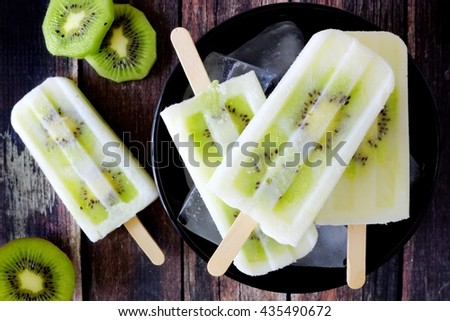 Bowl of kiwi vanilla yogurt popsicles on a dark rustic wood background - stock photo