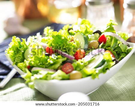 bowl of leafy green salad with olives, tomatoes and cucumber. - stock photo