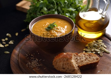 Bowl of lentil, carrot and pumpkin soup, a piece of bread and a bottle of olive oil on a wooden board - stock photo