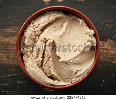 bowl of liver pate on old wooden table - stock photo