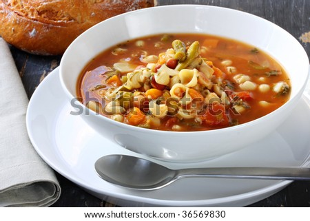 Bowl of minestrone pasta soup, on rustic table, with cob of tomato ...