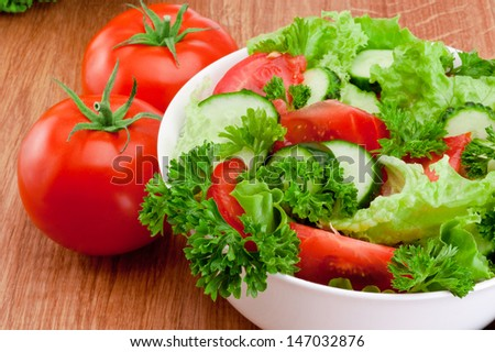Bowl of mixed salad against and Two tomatoes is wooden table - stock photo