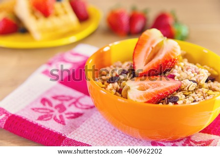 Bowl of muesli with strawberry on top of it - stock photo