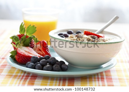 Bowl of muesli with yoghurt, strawberries and blueberries, boiled egg and orange juice for healthy breakfast