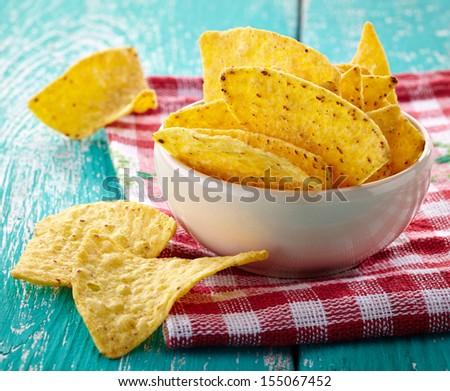 Bowl of nachos on blue wooden background - stock photo