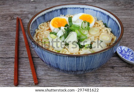 bowl of noodles with vegetables and soft boiled egg on wooden table. delicious noodle. Instant noodle. hot noodle. vegetarian noodle. hot noodle onion soup. Homemade Quick Ramen Noodles with egg. - stock photo