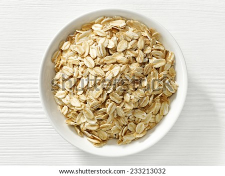 bowl of oat flakes on white wooden table - stock photo