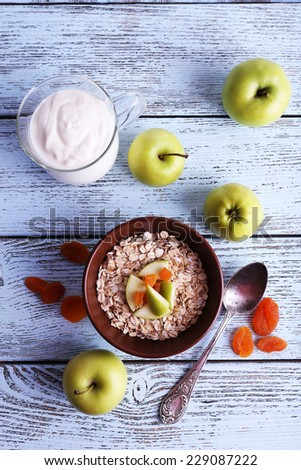 Bowl of oatmeal, dried apricots, apples and yogurt on blue wooden background - stock photo