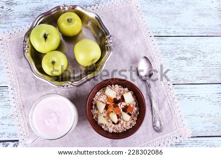 Bowl of oatmeal, dried apricots, apples and yogurt on napkin on blue wooden background - stock photo