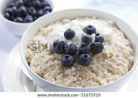 Bowl of oatmeal porridge, topped with fresh blueberries and yogurt.  Healthy, delicious variation of a traditional Scottish breakfast. - stock photo