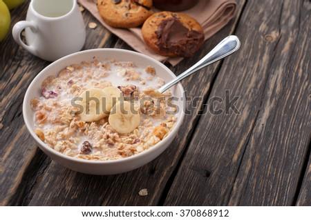 Bowl of oatmeal porridge with bananas on a dark rustic background closeup - stock photo