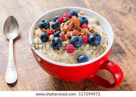 Bowl of oatmeal porridge with fresh blueberries, raspberries, muesli and almonds on wooden table. Healthy breakfast concept
