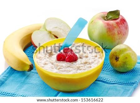 Bowl of oats porridge with fresh fruits. Baby food - stock photo