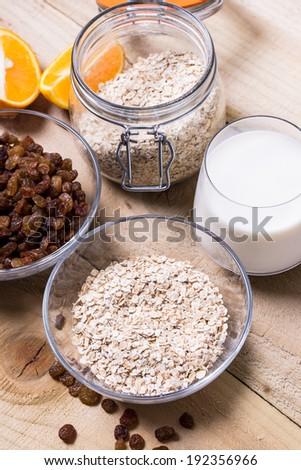 Bowl of oats, raisins cup of milk on the wooden table