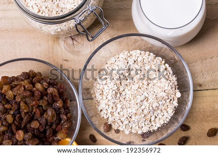 Bowl of oats, raisins cup of milk on the wooden table  - stock photo