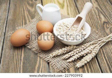 Bowl of oats with eggs and milk on a dark wooden background - stock photo