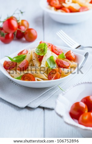 Bowl of pasta salad with cherry tomatoes on kitchen table - stock photo