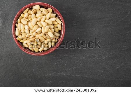 Bowl of pine nuts on a slate surface, view from above with copy space. - stock photo