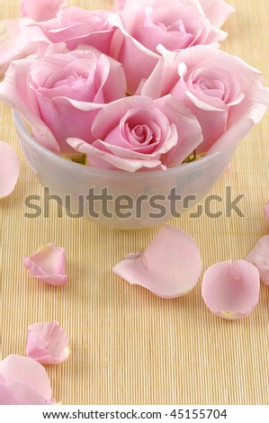 bowl of pink rose and petals on towel
