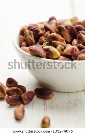 Bowl of pistachio on wooden surface - stock photo