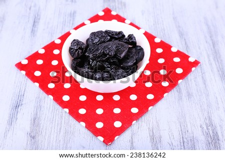 Bowl of prunes on polka-dot napkin on color wooden background - stock photo