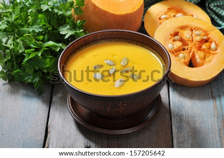 Bowl of pumpkin soup on rustic wooden table. - stock photo