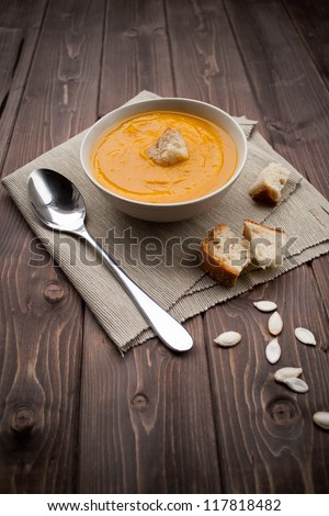 Bowl of pumpkin soup with bread crouton on white wood table - stock photo
